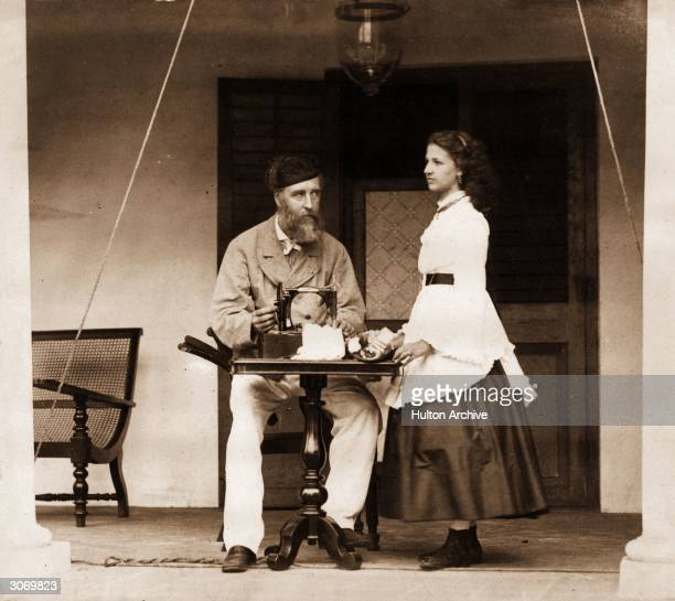 Lieutenant Colonel Augustus William Ritherdon plies a sewing machine in Madras watched by his daughter