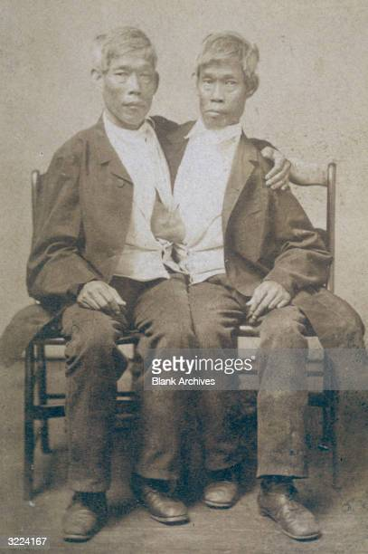 Portrait of American Siamese twins Chang and Eng Bunker sitting on two wooden chairs Born in Siam the twins toured with carnivals in the United...