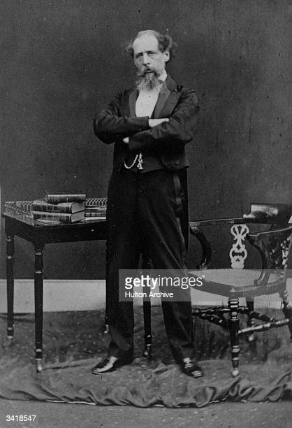 Charles Dickens English novelist in later life dramatically posed standing in front of a table covered in books