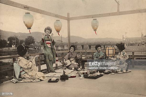 A group of Japanese women enjoy a picnic outdoors on the Kamogawa in Kyoto southern Honshu