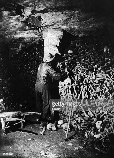 A man working in the catacombs of Paris in one of the first pictures taken by artificial lights by Nadar A large pile of human bones and skulls fill...
