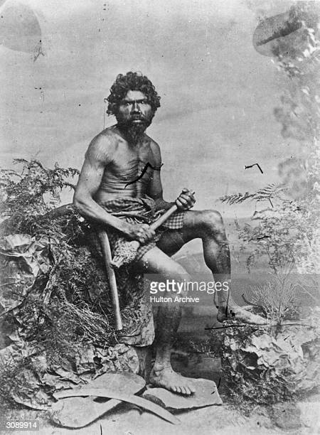 An aborigine or indigenous Australian with a boomerang lying beside him
