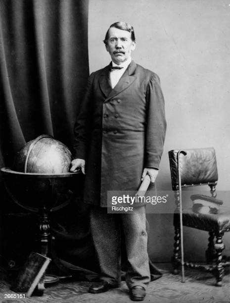 David Livingstone Scottish doctor and missionary standing next to a globe symbolising his achievements as one of the most important explorers of...