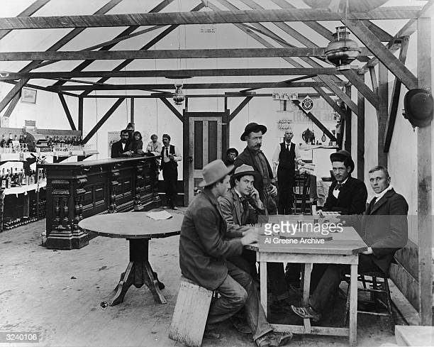 Interior view of a saloon where a group of men sit gambling at a table and workers pose in the background