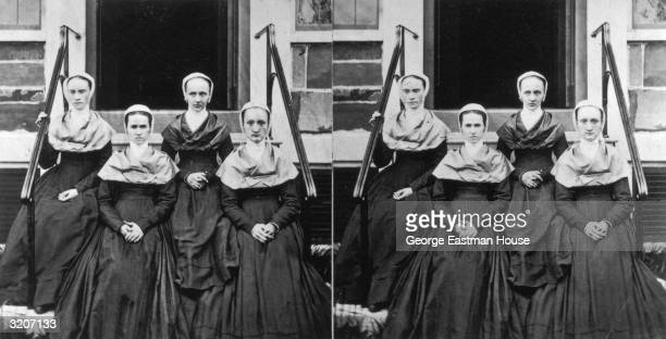 Portrait of four Quaker women sitting on the front steps of a building, Lebanon, U.S.A. They wear matching outfits, consisting of long dark dresses,...