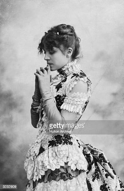 Studio portrait of Italian actor Eleonora Duse standing in profile holding her hands to her lips and looking down Duse is wearing a gown with layers...