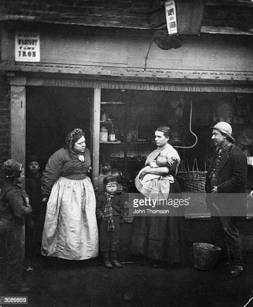 Impoverished people in front of a rag shop in Lambeth London where the Thames annual tidal overflow causes hardship to the locals 'Sufferers From The...