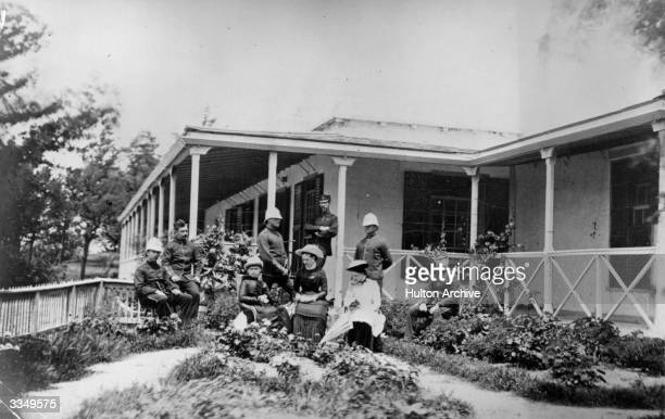 A group of British expatriots some in military uniform sitting outside their house in India