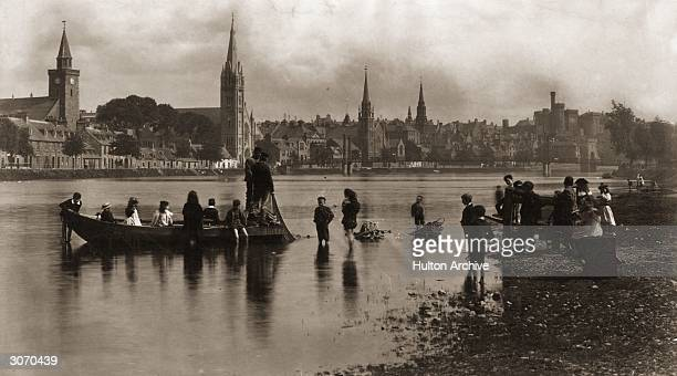 Children paddle out to a rowing boat at Friar's Shott, Inverness with several churches and the castle along the far river bank.