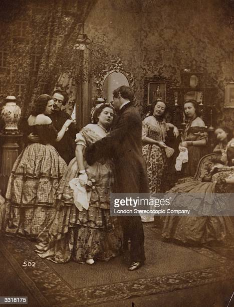 Couples dancing and kissing under the mistledoe at a soiree in Victorian times.