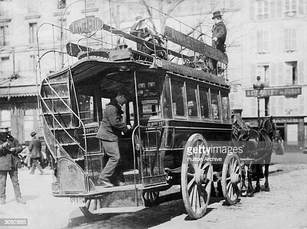 French author and poet Victor Hugo standing with his hand shading his eyes aboard a horsedrawn omnibus The writer is supposed to have completed a...