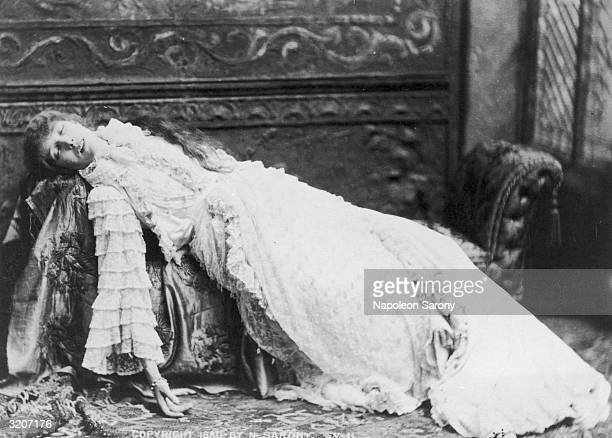 Fulllength portrait of French actor Sarah Bernhardt wearing a ruffled nightgown reclining on a chaise longue with her eyes closed as if she had...