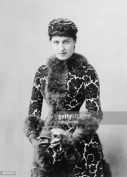 Halflength portrait of English actor socialite and racehorse owner Lillie Langtry wearing a brocaded fur trimmed coat with matching muff and hat...