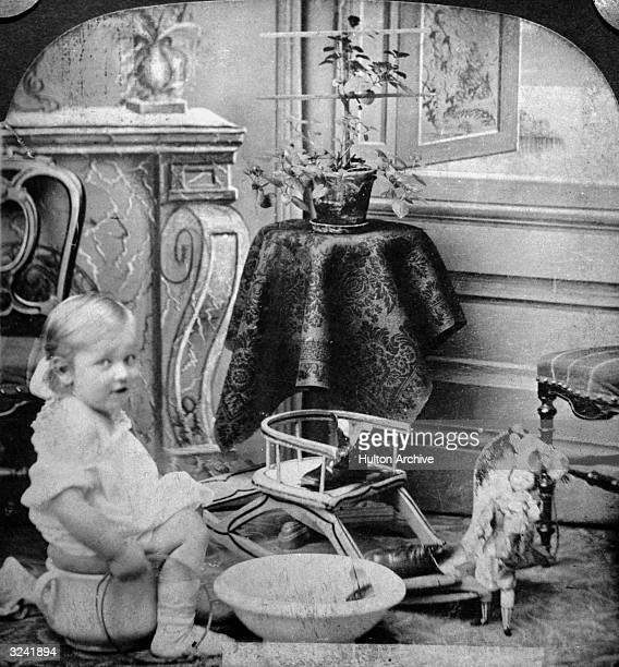 An infant girl sits on a large ceramic pot while toilet training by an open window