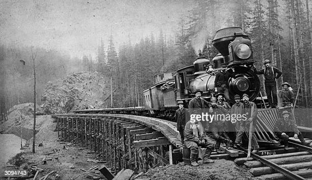 Members of a Northern Pacific Railroad crew including a Chinese man in the foreground pose alongside a Baldwin locomotive