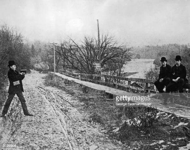 A boy takes a picture of two boys sitting on a bridge railing over the Genesee River with one of the first Kodak cameras Rochester New York The...