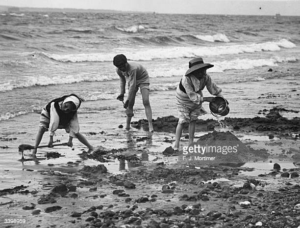 A group of children playing on the beach with a bucket and spades