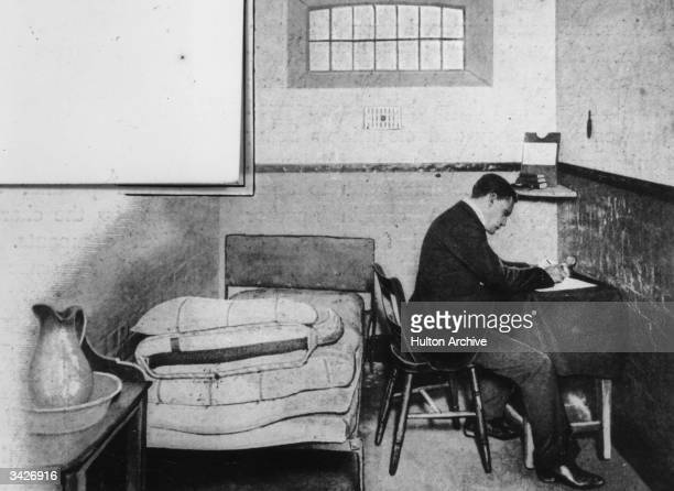 A man in Holloway prison cell is writing his defence at a small table The only other furniture is a bed and a wash stand with basin and ewer