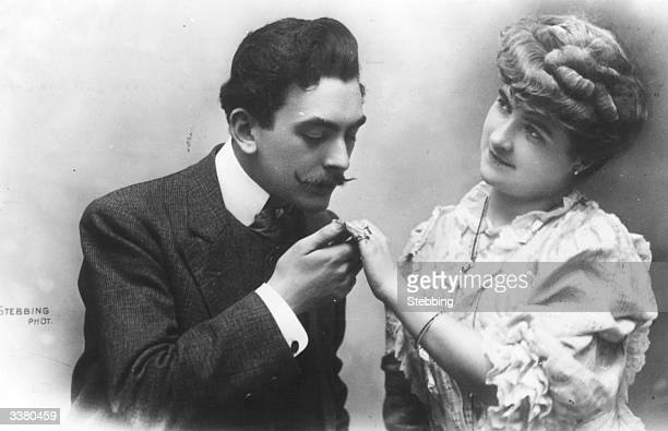 A moustached man kisses the hand of his sweetheart