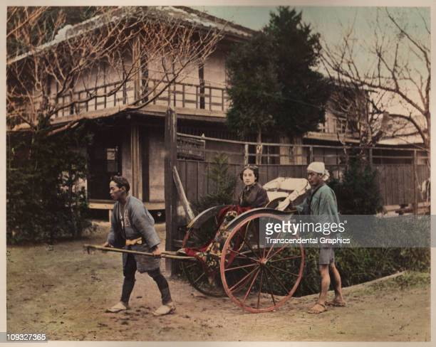 TOKYO circa 1890 A rickshaw driver brings a wealthy young woman to her destination as her man servant accompanies on foot in this circa 1890 hand...