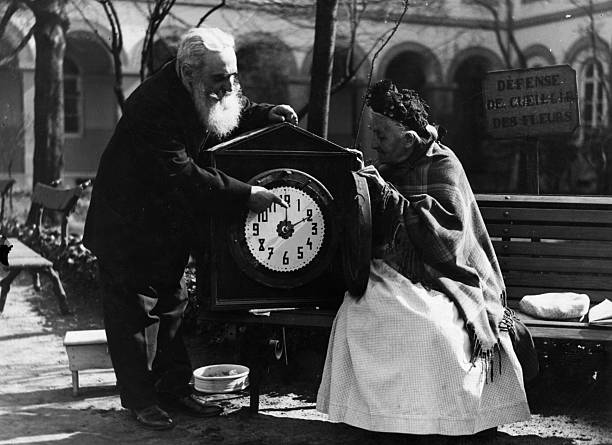 An old man changes the hands of a clock for summertime....