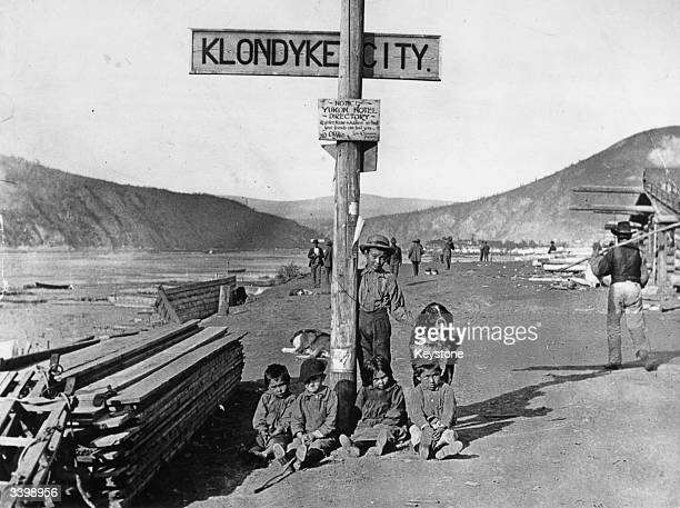 Children of the Klondike area of Yukon Territory Canada sitting with their dog by a street sign In the 1890's there was a great gold rush here...