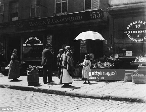 Dutch-born photographer and social reformer Jacob Riis snaps a photograph in front of a vegetable stand and the post office on 55 1/2 to 57 Mulberry...