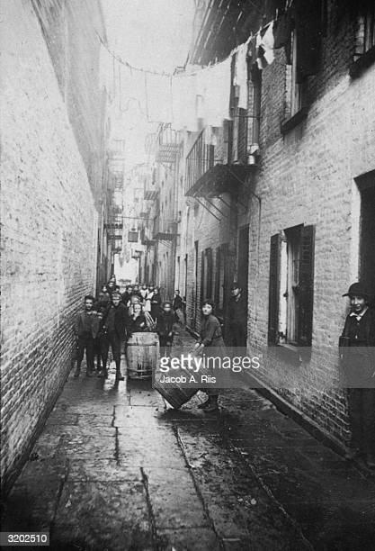 Fulllength image of children standing with barrels in an alley strewn with clotheslines at the Gotham Court tenement 3638 Cherry Street New York City...
