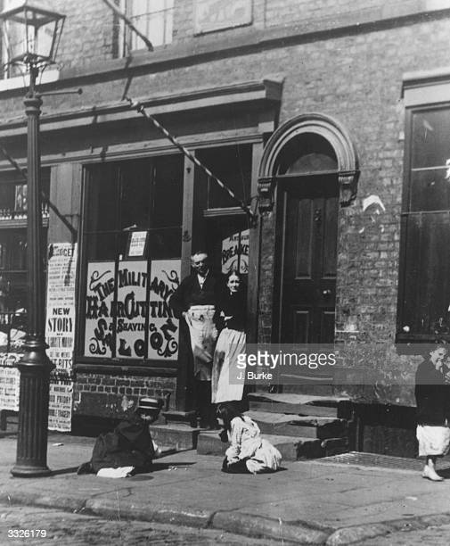 In a Liverpool street children are playing 'Jacks and Allies' outside a barber's shop with its striped pole