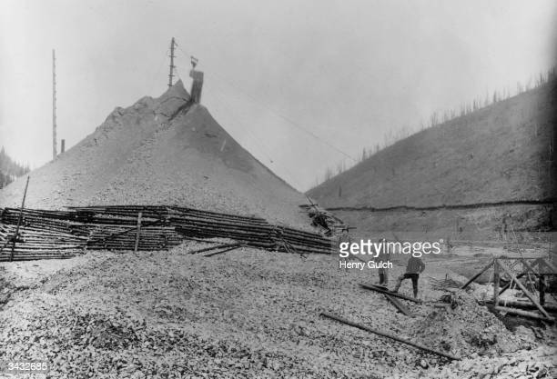 Miners standing next to a slag heap below Disc Miller Creek in a Klondike gold mine in Canada Powlesland_Collection