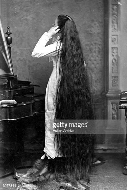 Miss Milo standing in front of a dressingtable Her very long hair touches the ground