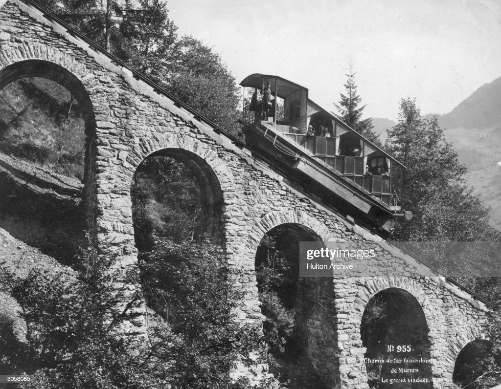 Passengers travelling up the grand viaduct at Murren, Switzerland on a steep funicular railway.