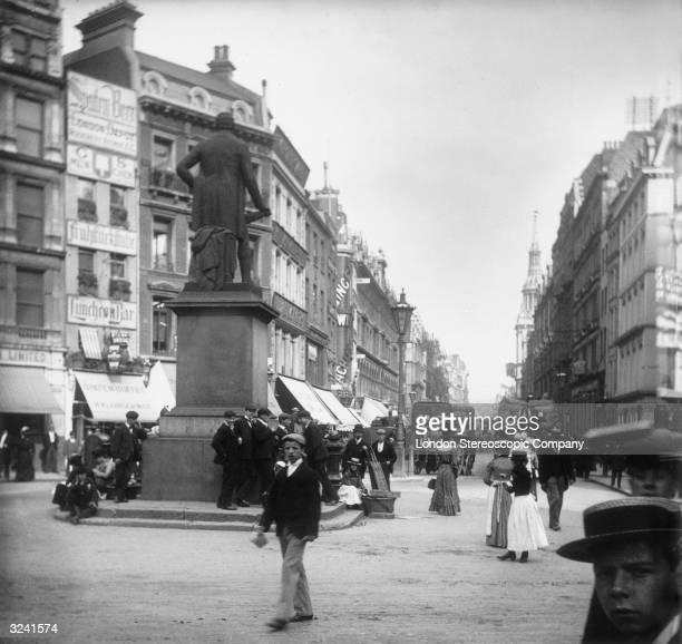 Pedestrians on London's Cheapside near the statue of Robert Peel