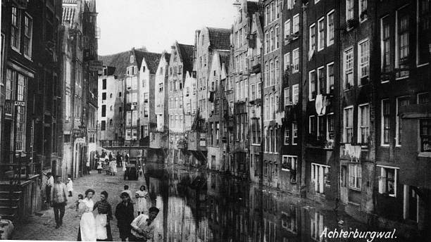 Pedestrians walk along a towpath flanked by tall houses...