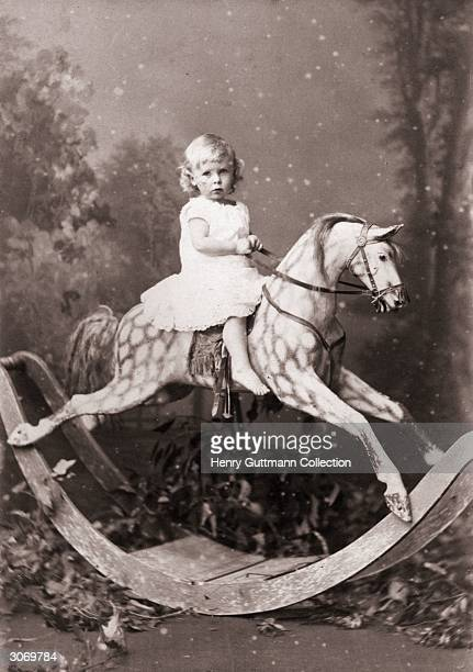 Windham Baring aged one year and nine months on a large dappled rocking horse He is dressed in a frock and has bare feet