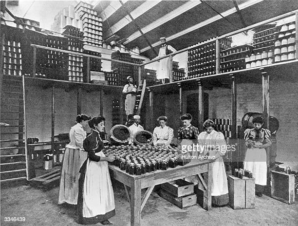 Women packing syrups and fruit delicacies into glass jars at a bottling plant