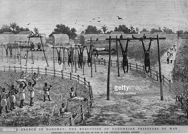 Dahomeian prisoners of war executed by the French hanging by their feet from scaffolds in the Uhunglo market Abomey Scavenging birds are hovering...