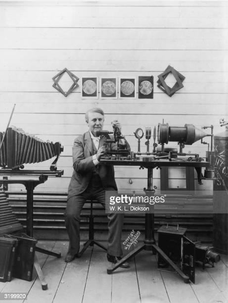 American inventor Thomas Edison holds up and looks at a slide while sitting behind a microscope under enlarged microscopic images on the wall during...