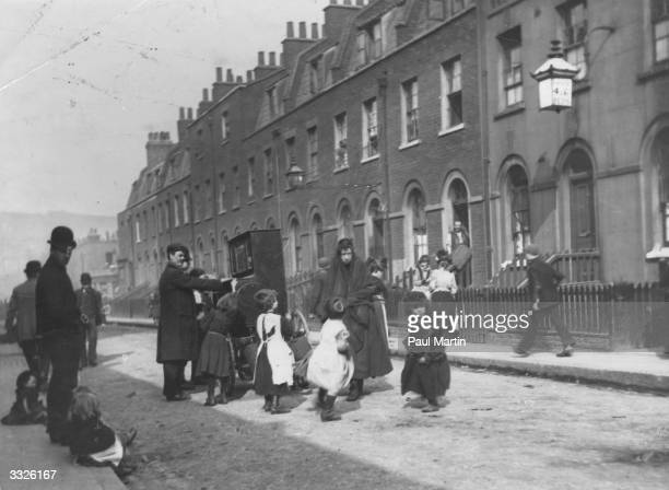 Children dancing to the Pas de Quatre a famous Gaiety piece played by an organ grinder in a London street