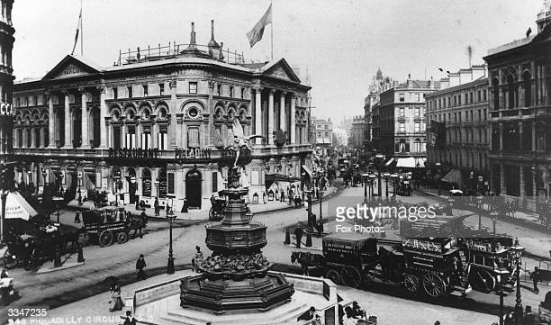 A scene at the busy Piccadilly Circus in London with the statue of Eros at the centre and a variety of traffic including horse drawn trams passing...