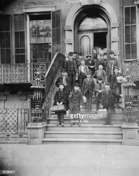 A group of men and young boys stand outside the front entrance of the Children's Aid Society's central office at 24 St Mark's Place New York City The...