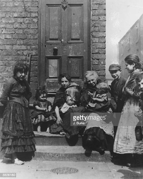 A ragged group sitting on a doorstep in a Liverpool slum