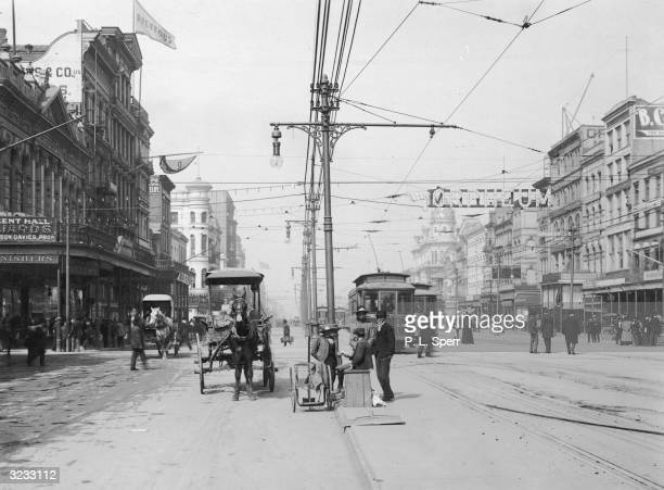 A view of Canal Street with trolleys running on overhead lines and horsedrawn carriages New Orleans Louisiana 1890s A sign for the Orpheum Theatre...