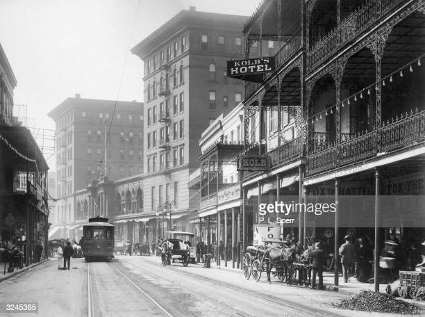 View of St. Charles Street, showing the terraced exterior of Kolb's Hotel, with streetcars and horsedrawn carriages in the street, New Orleans,...