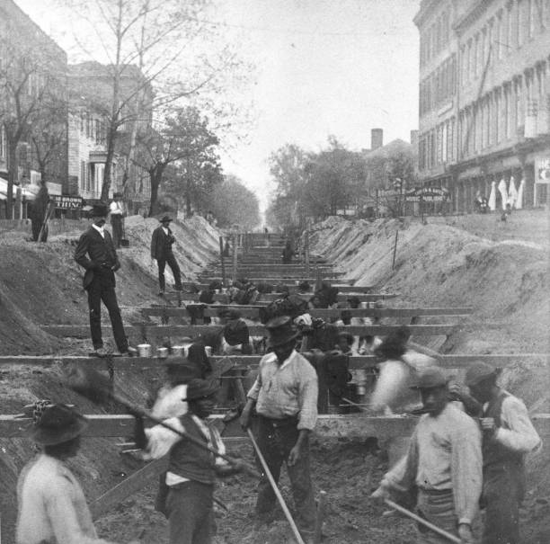 African-American workers dig a sewer down the middle...