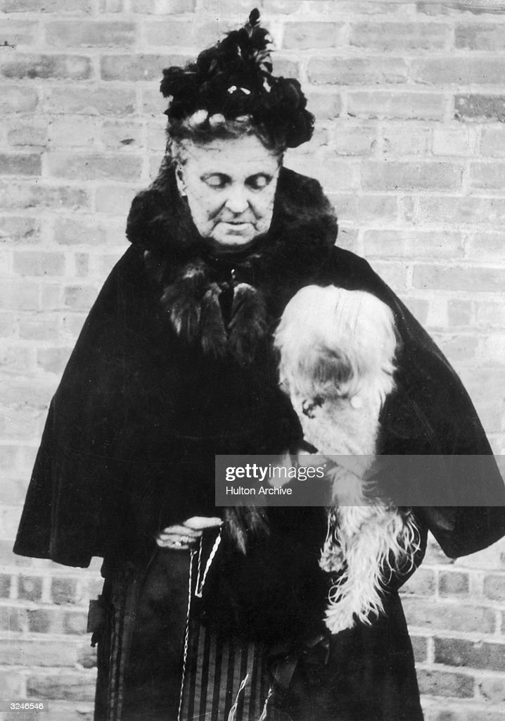American financier Hetty Green (1835-1916) stands in front of a brick wall, holding her beloved pet dog.