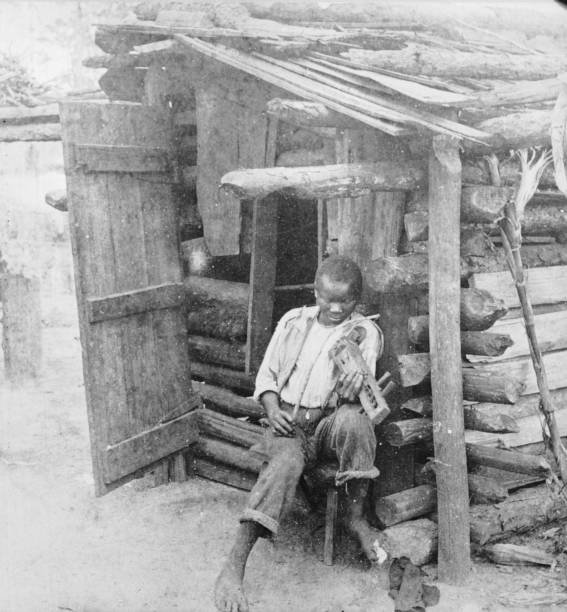 An African-American boy sits by the door of a wooden...