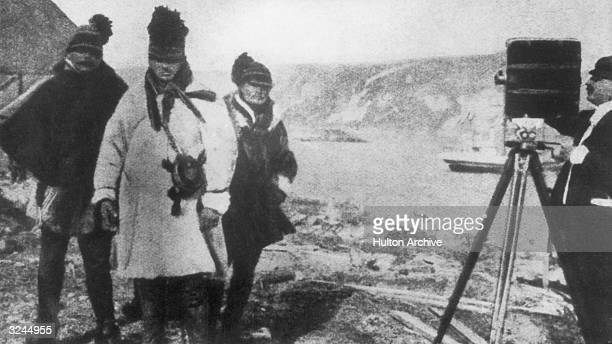 Felix Mesguich, one of the first commercial cameramen, stands behind a motion picture camera, filming three men outdoors in Lapland, northern...