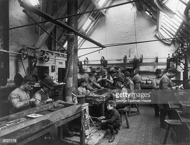 Fulllength image of immigrants possibly of Russian and eastern European origins working in a metal shop in the United States A boy stokes a coal...