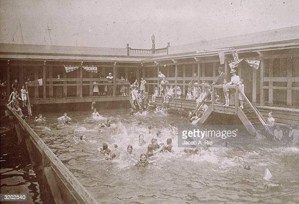 Children swim under the supervision of adults at Public Bath located at the Hudson River on 51st Street in New York City 'Teaching the Girls to Swim...